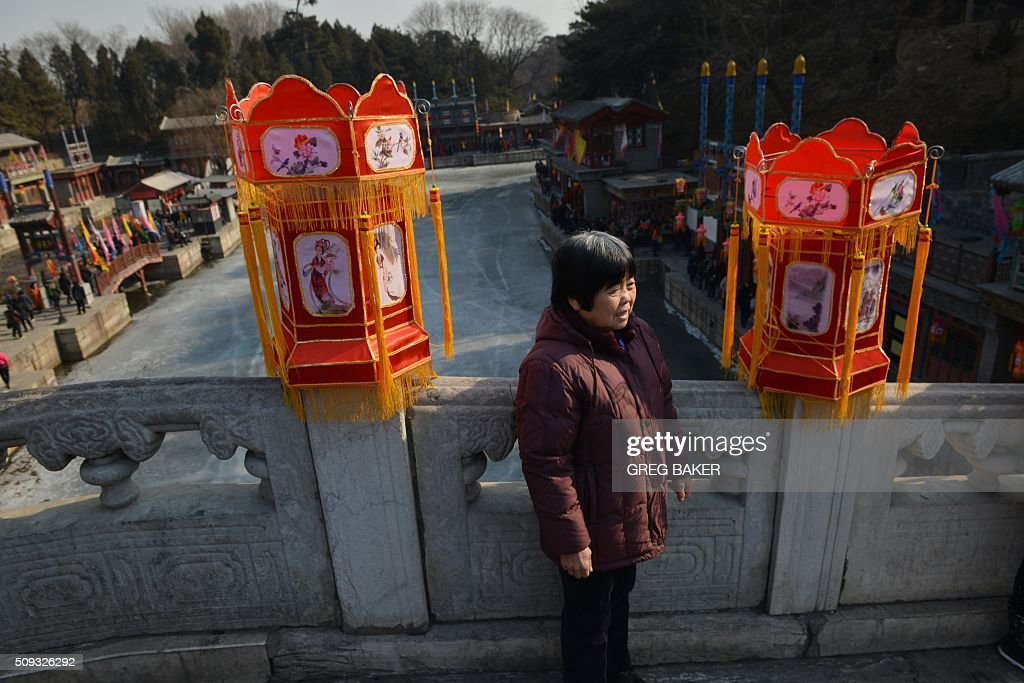 A woman poses for photos on the bridge above a frozen lake at the Summer Palace during Lunar New Year celebrations in Beijing on February 10, 2016. Millions of Chinese are celebrating the 'Spring Festival', the most important holiday on the Chinese calendar, which this year marks the beginning of the Year of the Monkey. AFP PHOTO / GREG BAKER / AFP / GREG BAKER