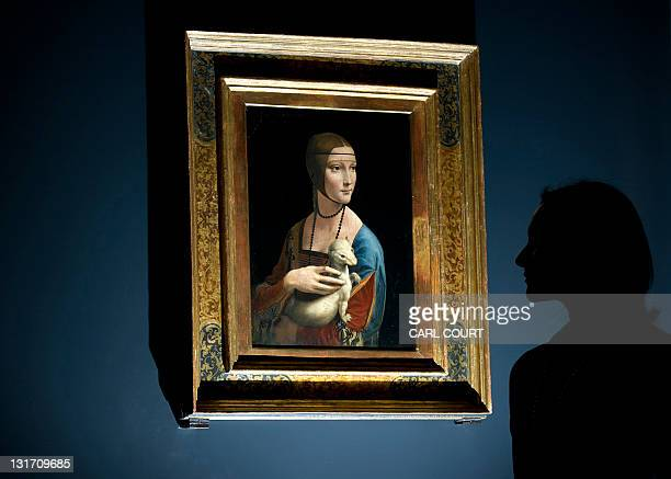 A woman poses for pictures beside a painting entitled 'Portrait of Cecilia Gallerani' by Italian artist Leonardo da Vinci during a photocall at the...