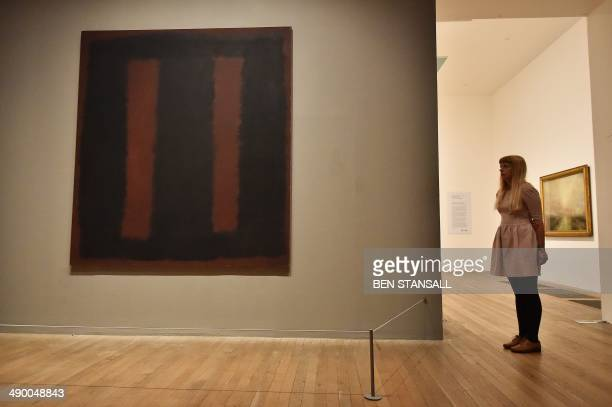 A woman poses for pictures beside a work of art by Russian born US artist Mark Rothko entitled 'Black on Maroon' 1958 during a photocall at the Tate...