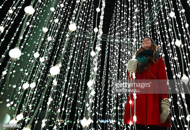 A woman poses for pictures in a light display during a photocall at Kew Gardens in south west London on November 24 during their launch of the...