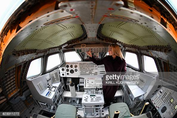 A woman poses for pictures inside the cockpit of one of the Soviet era space shuttles Buran installed in a museum at Russianleased Baikonur...