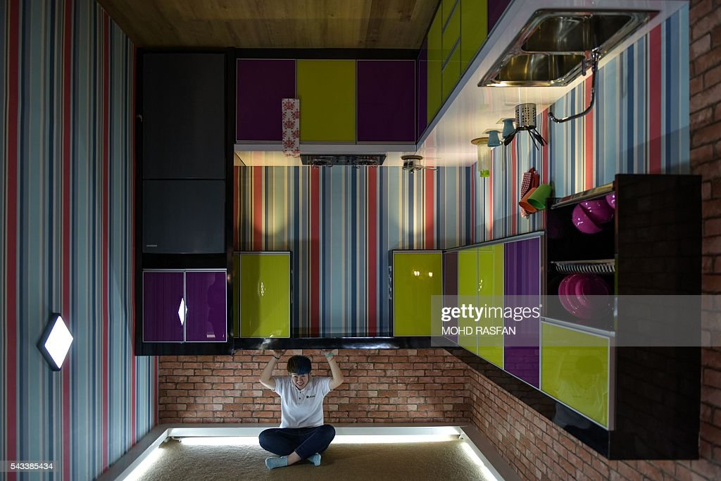 A woman poses for pictures inside the Kuala Lumpur Upside Down House at KL Tower in Kuala Lumpur on June 28, 2016. Kuala Lumpur Upside Down House is a two-storey house and is the latest attraction for tourists arriving to the Malaysian capital where everything inside such as the furniture are placed in an upside down position. / AFP / MOHD