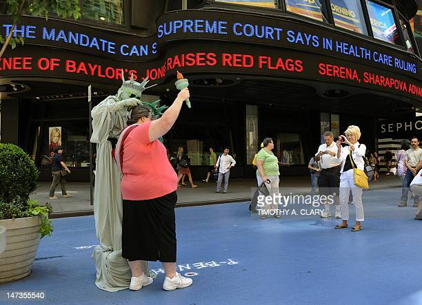 A woman poses for pictures with a man dressed as the Statue of Liberty as the ABC Television Times Square Studios tickertape reports the news on the...