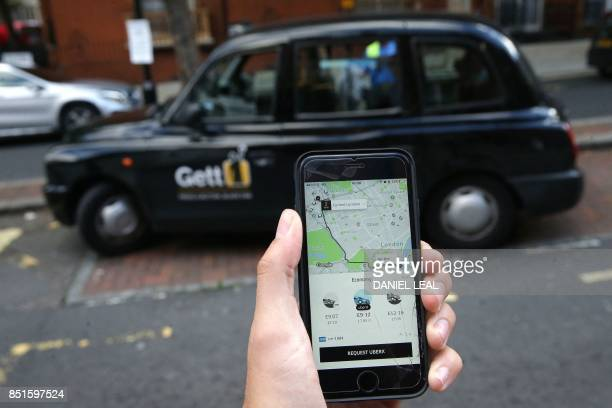 A woman poses holding a smartphone showing the App for ridesharing cab service Uber in London on September 22 2017 London transport authorities...