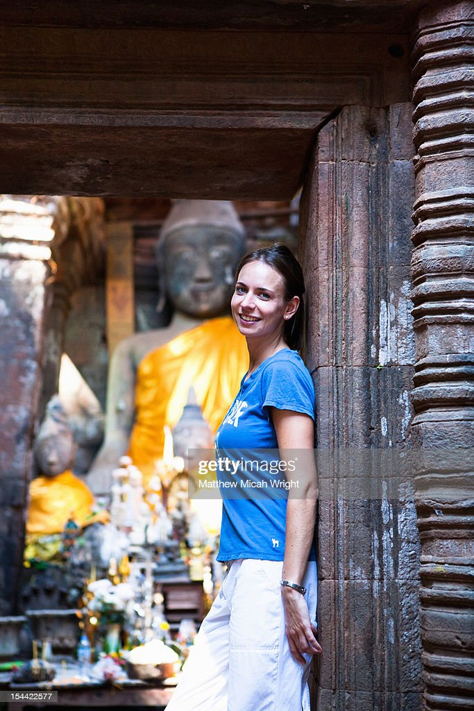 A woman poses in front of ancient ruins. : Stock Photo