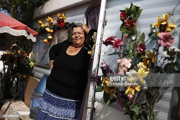A woman poses in front of her caravan in a Roma camp set up in SaintDenis northern Paris suburbon October 4 2015 AFP PHOTO / THOMAS SAMSON