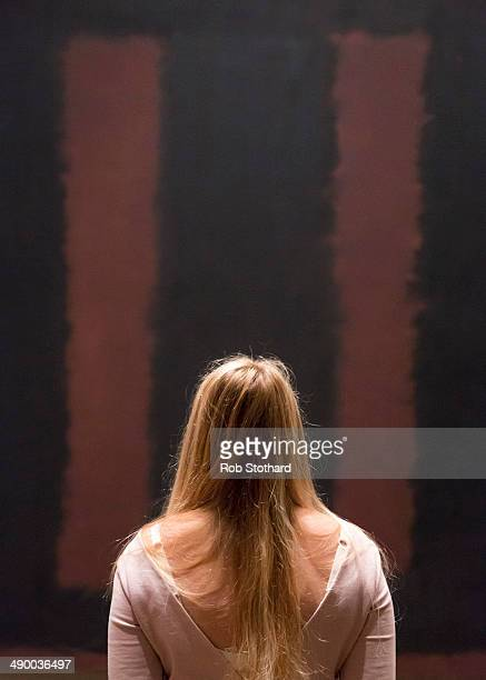 A woman poses in front of Mark Rothko's painting Black On Maroon 1958 after going back on display at Tate Modern gallery 18 months after it was...