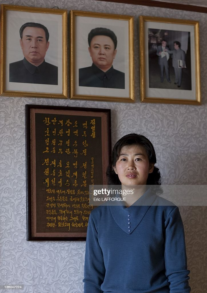 A woman poses in front of portraits Kim Jong Il and Kim Il Sung on May 7, 2010 in Ri village, Jung Pyong, North Korea. She once received a visit to her home from Kim Jong Il.