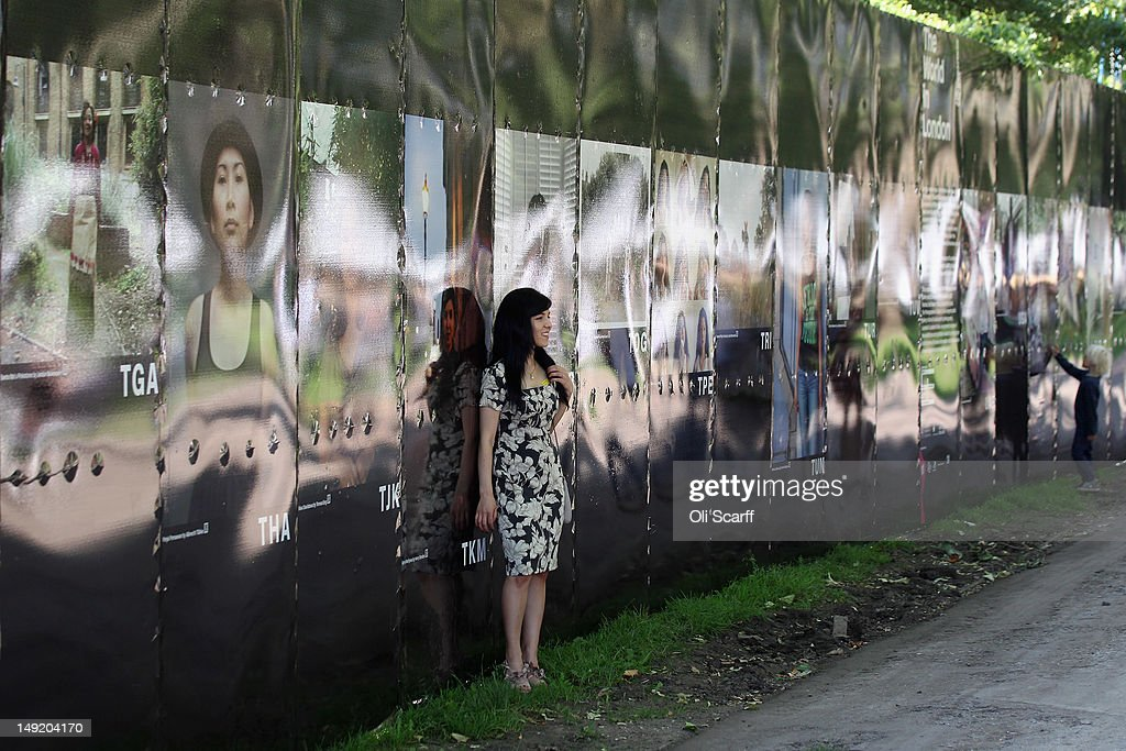 A woman poses in front of the photography exhibition 'The World in London' in Victoria Park on July 25, 2012 in London, England. The project, initiated by The Photographers' Gallery, aimed to commission portraits of 204 Londoners, each originating from one of the nations competing in the London 2012 Olympic Games. The project has taken three years to come to fruition and the Photographers' Gallery is still seeking to find sitters from six nations to complete the full set, namely: American Samoa, FS Micronesia, Guam, Marshall Islands, Nauru and Palau.