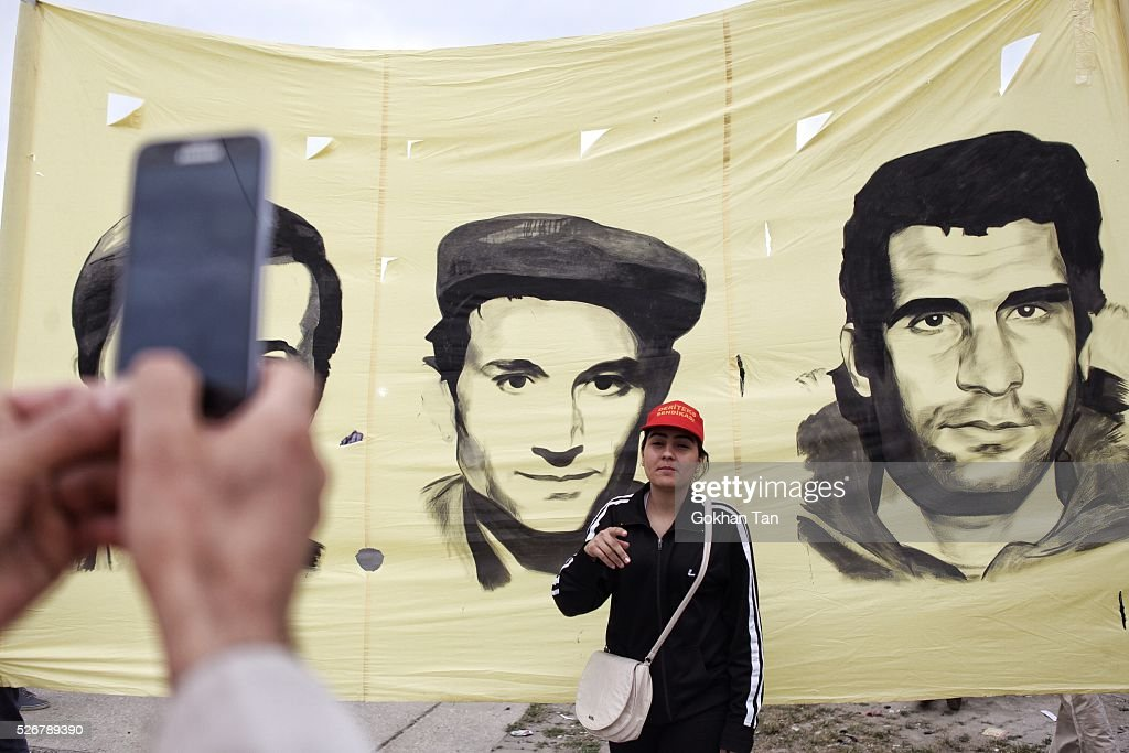 A woman poses in front of the poster of Turkish revolutonaries Deniz Gezmis, Huseyin Inan and Yusuf Aslan in Istanbul's Bakirkoy district during May Day celebrations on May 1, 2016 in Istanbul, Turkey. Turkish police used tear gas and water cannon to disperse protesters as they tried to make their way to Taksim Square and other protest points.
