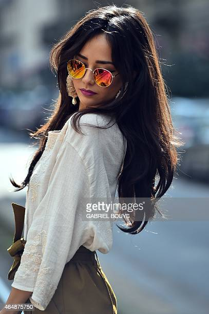 A woman poses in the street before the show for fashion house Dolce Gabbana at the women Fall / Winter 2015/16 Milan's Fashion Week on March 1 2015...