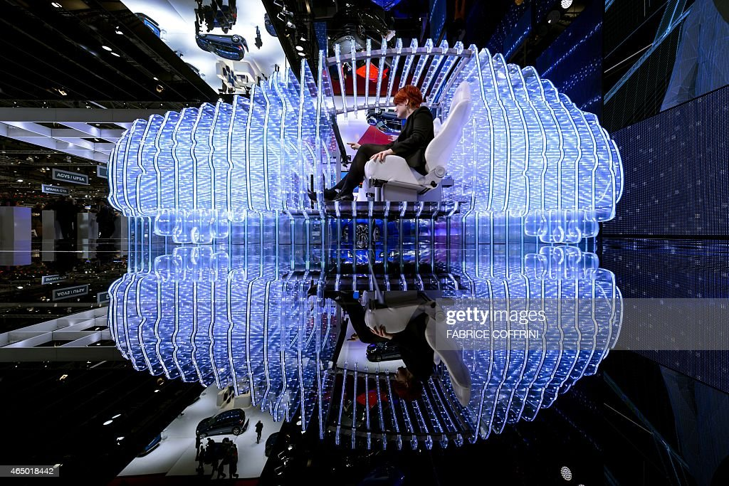 A woman poses inside the mockup of a car at the Opel booth during the press day of the Geneva Car Show on March 3 2015 in Geneva The show runs...
