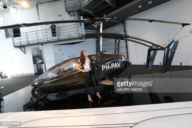A woman poses near the 'PalV Liberty' flying car a gyrocopter with three wheels and a retractable rotor on display as part of the 'Top Marques' show...