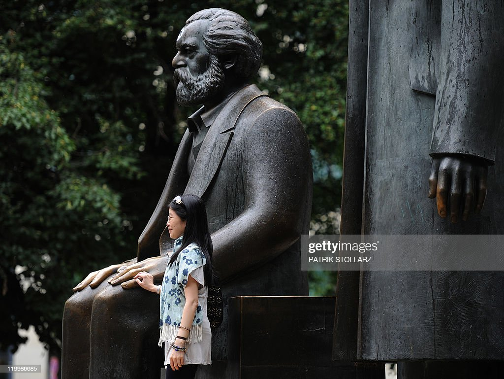A woman poses next to a bronze statue of German philosopher, sociologist and economic historian Karl Marx on July 28, 2011 in Berlin. The monument, which also includes a statue of German industrialist and social scientist Friedrich Engels, has become an icon of the early communism ideology. It was built by east German sculptor Ludwig Engelhardt and inaugurated in 1986.