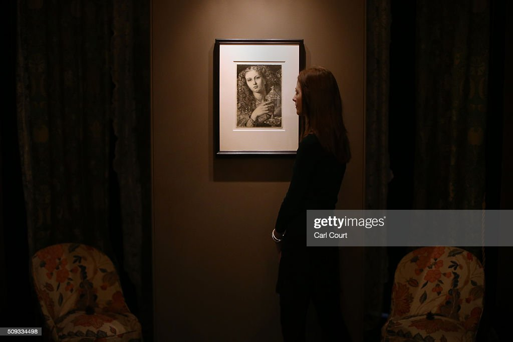 A woman poses next to a picture by Frederick Sandys entitled 'King Pelles' Daughter Bearing the Vessel of the Sanc Graal' during a preview at Leighton House Museum on February 10, 2016 in London, England. The worst form part of the Pre-Raphaelites on Paper exhibition, which will run from 12th February to 29th May 2016.