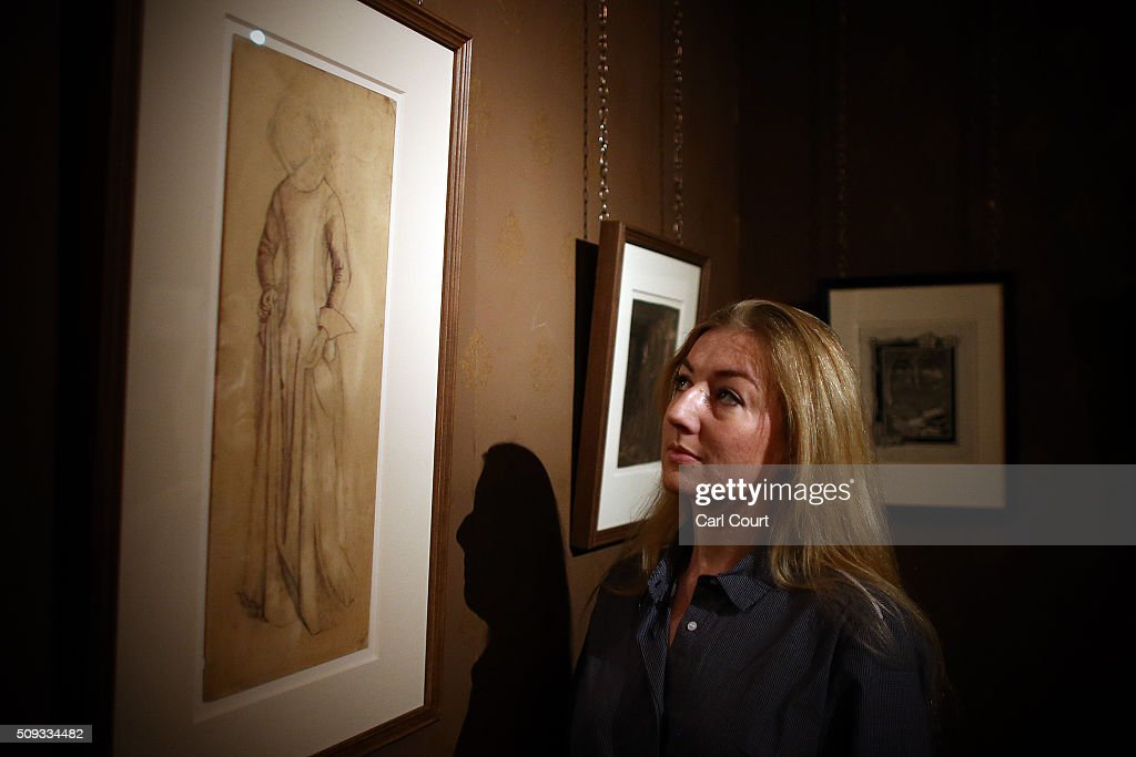 A woman poses next to a picture by William Morris entitled 'Study for La Belle Iseult' during a preview at Leighton House Museum on February 10, 2016 in London, England. The worst form part of the Pre-Raphaelites on Paper exhibition, which will run from 12th February to 29th May 2016.
