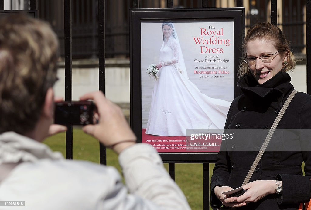 A woman poses next to a poster advertising the display of Kate Middleton's royal wedding dress outside Buckingham Palace in central London as the palace opens its doors to the public for the summer on July 23, 2011, to showcase highlights including the dress worn by Kate Middleton when she married Prince William in April. It was the best kept secret of the royal wedding, but now the Alexander McQueen dress worn by the former Kate Middleton when she married Prince William is being put on public display for all to admire. Catherine's ivory and white satin-gazar dress, designed by Sarah Burton, goes on show at Buckingham Palace as part of the annual summer opening, where hundreds of thousands of visitors are expected to flock to see it.