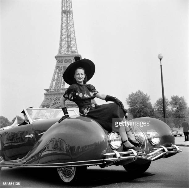 A woman poses on a car during an elegance contest in Paris in 1948 / AFP PHOTO /