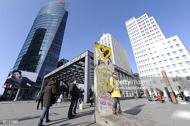 A woman poses on a single slab of the former Berlin wall placed on the wall's original path in Berlin's now thriving Potsdamer Platz October 20 2009...
