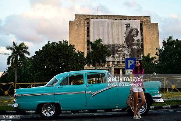 A woman poses with a car in front of the Cuban national library with its facade with the Cuban flag at half mast and a picture of Cuban revolutionary...