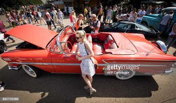 A woman poses with a classic automobile during the Faces and Laces alternative modern art festival on August 12 2017 in the Gorky Central Park of...