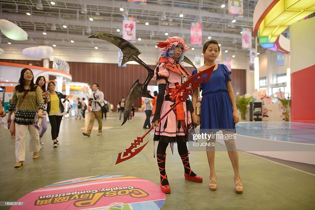 A woman poses with a man in costume at a Cosplay expo in Xiamen, Fujian province on October 25, 2013. Cosplay is a social phenomenon originating in Asia in which participants wear costumes representing a character or trend. AFP PHOTO / Ed Jones