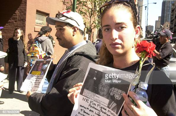 A woman poses with a picture of a missing loved one who was last seen at the World Trade Center on September 11 2001