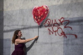 A woman poses with a piece of street art which depicts a heartshaped balloon covered in bandages and was allegedly done by the street artist Banksy...