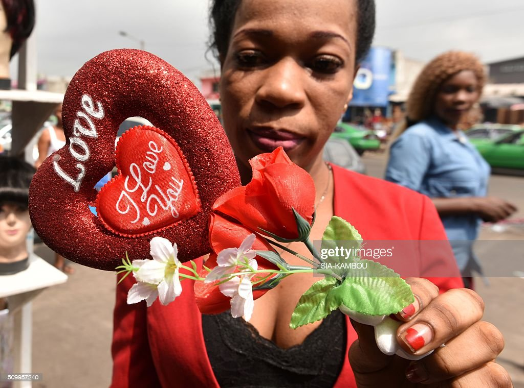 A woman poses with a Valentine's day item on February 13, 2016 in a street market in Marcory, a popular suburb of the Ivorian capital. / AFP / SIA-KAMBOU