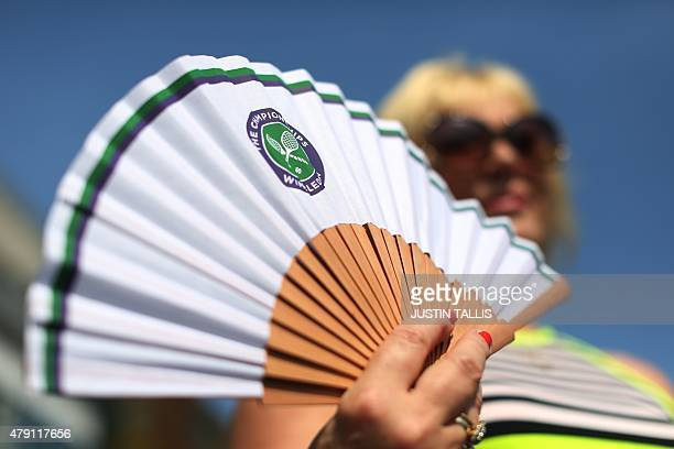 A woman poses with a Wimbledon fan at The All England Tennis Club on day three of the 2015 Wimbledon Championships in Wimbledon southwest London on...