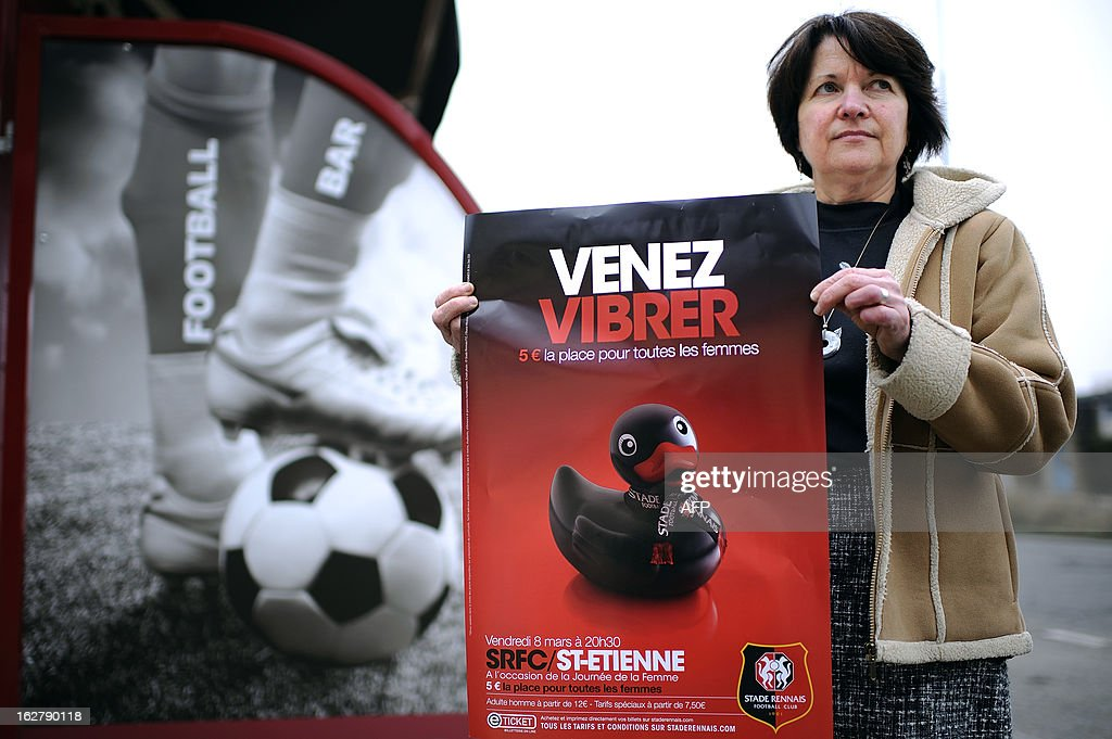 A woman poses with an advertising poster of the Stade Rennais football club showing a sex toy and reading 'come to vibrate' on February 27, 2013 in Rennes, western France