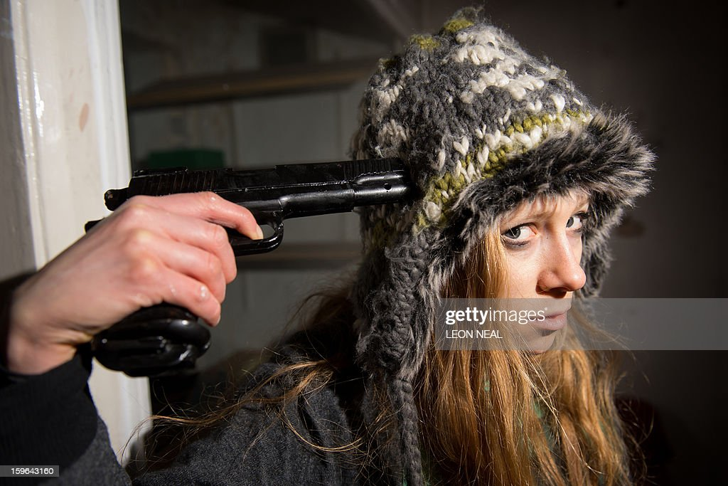 A woman poses with an entirely edible replica pistol made of chocolate at a film set pop-up experience in east London, on January 17, 2013. The event was held to promote the release of a new horror film, 'The Helpers'. AFP PHOTO / LEON NEAL