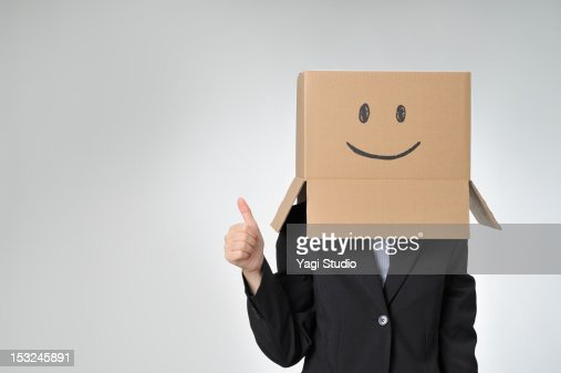 Woman poses with cardboard box over her head. : Stock Photo