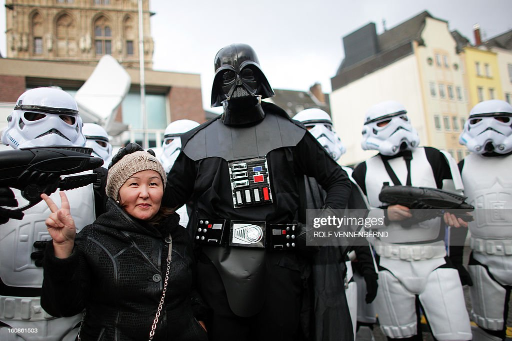 A woman poses with fools dressed as Darth Vader and star troopers during the beginning of the street carnival in Cologne, western Germany on February 7, 2013, as the hot carnival season was launched. Hundreds of thousands of Germans, mainly in the western Rhine region, crowd the streets to celebrate Women's Carnival Day.