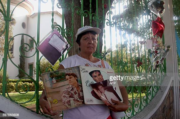 A woman poses with her albums of Mexican singer Juan Gabriel in front of his house in Ciudad Juarez Mexico on August 29 2016 Mexican singer composer...