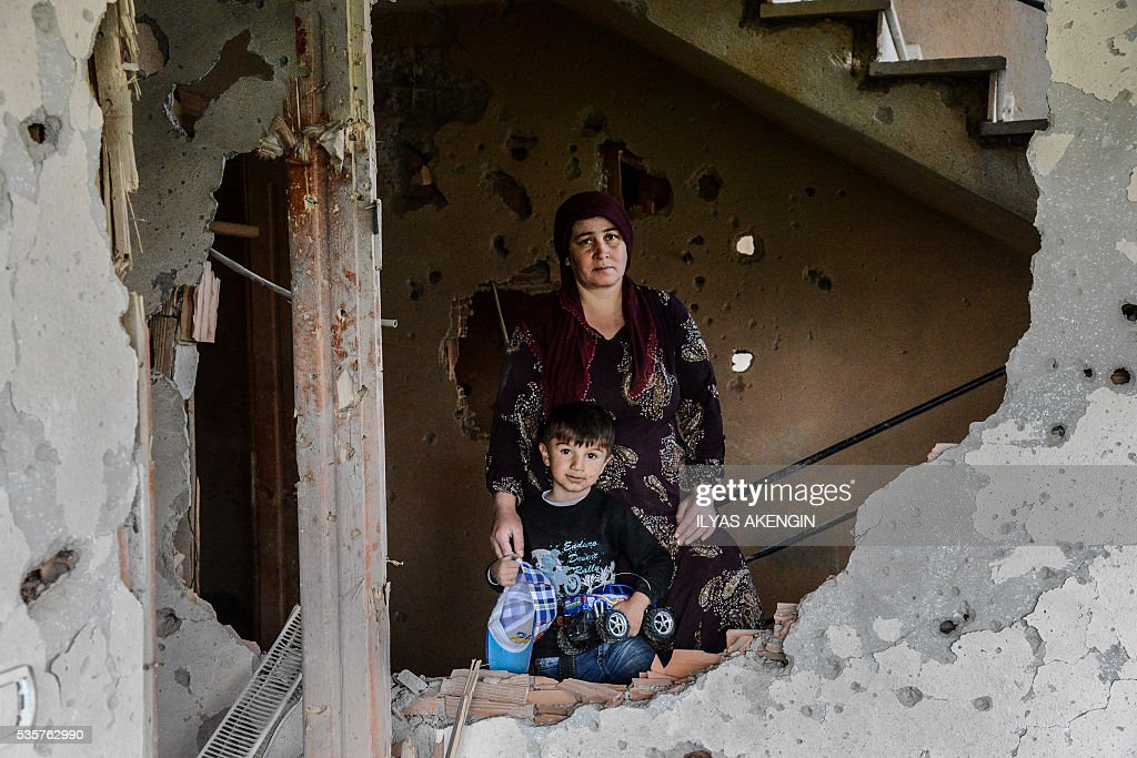 A woman with her child stay inside her damaged house following heavy fightings between government troops and Kurdish fighters after the curfew on May 30, 2016 in the majority Kurdish city town of Yuksekova, southeastern Turkey near the border with Iraq and Iran. / AFP / ILYAS