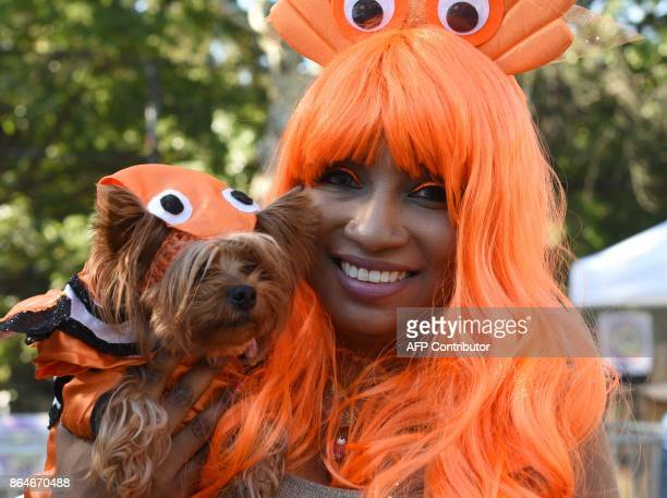 A woman poses with her dog dressed in costume during the 27th Annual Tompkins Square Halloween Dog Parade in Tompkins Square Park in New York on...
