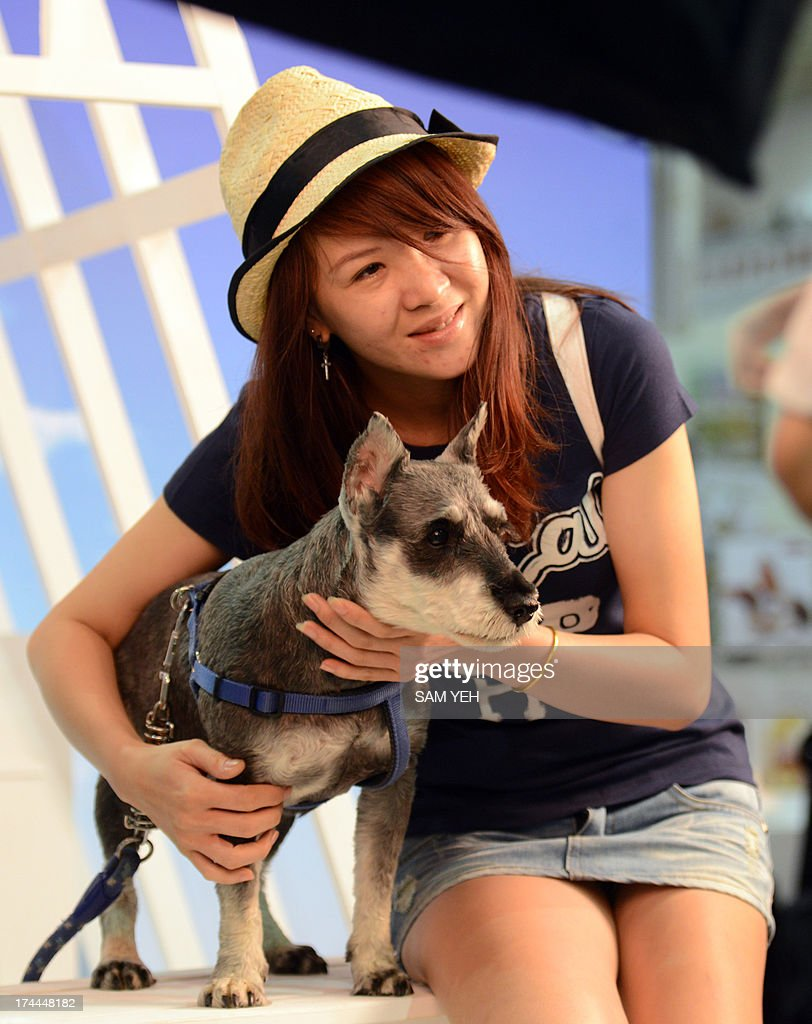 A woman poses with her dog for photo at a pet studio booth during the annual pet show at the World Trade Center in Nankang district, Taipei on July 26, 2013. More than 150 booths for dogs and cats have been set up for the exhibition which takes place from July 26-29. AFP PHOTO / Sam Yeh