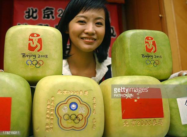 A woman poses with homegrown squareshaped watermelons during a press conference in Taipei 17 October 2007 The man said his company has received...