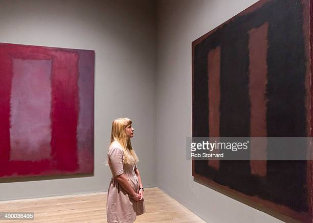 A woman poses with Mark Rothko's painting Black On Maroon 1958 after going back on display at Tate Modern gallery 18 months after it was vandalised...