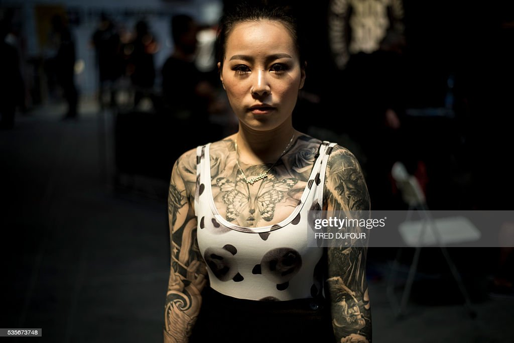 A woman poses with tattoos at the Langfang International Tattoo show, in Hebei province, on May 29, 2016. / AFP / FRED