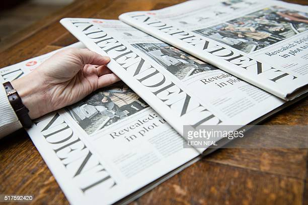 A woman poses with the final print edition of the Independent newspaper in London on March 26 2016 The final print edition of The Independent...
