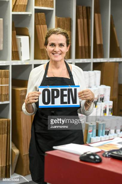 Woman posing at her franchise of retail shipping, postal, printing and business service center
