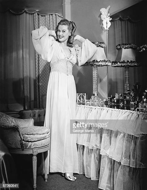 Woman posing by vanity table in opulent bedroom, (B&W), portrait