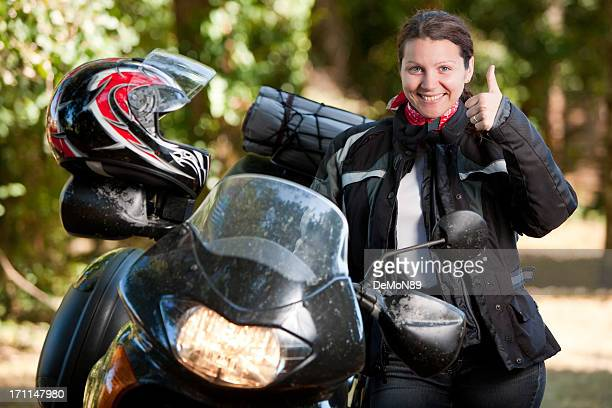 Woman posing happily next to her motorcycle