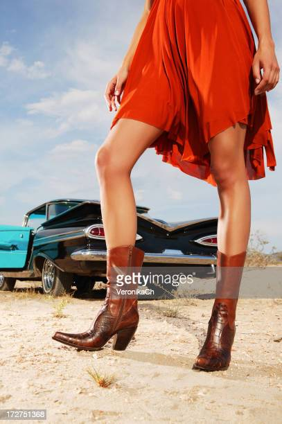 Woman posing in orange dress and boots beside classic car