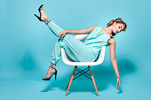 Elegant and beautiful woman posing sitting on a chair in the Pin-Up style.