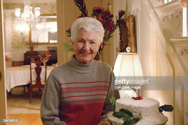 Woman posing with cake at home at Christmas
