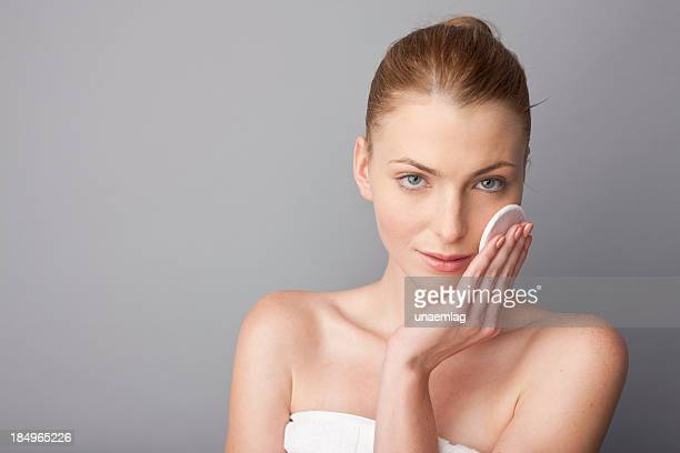 Woman posing with facial cosmetic pad