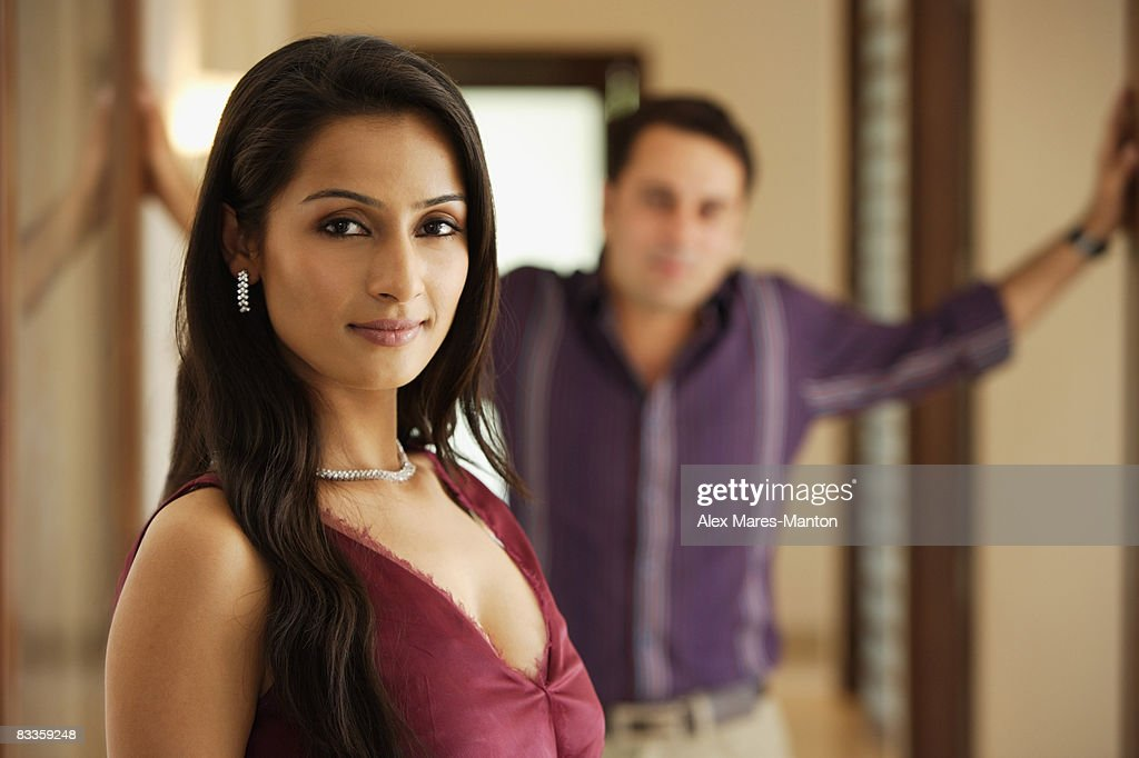 woman posing, with man behind her : Stock Photo